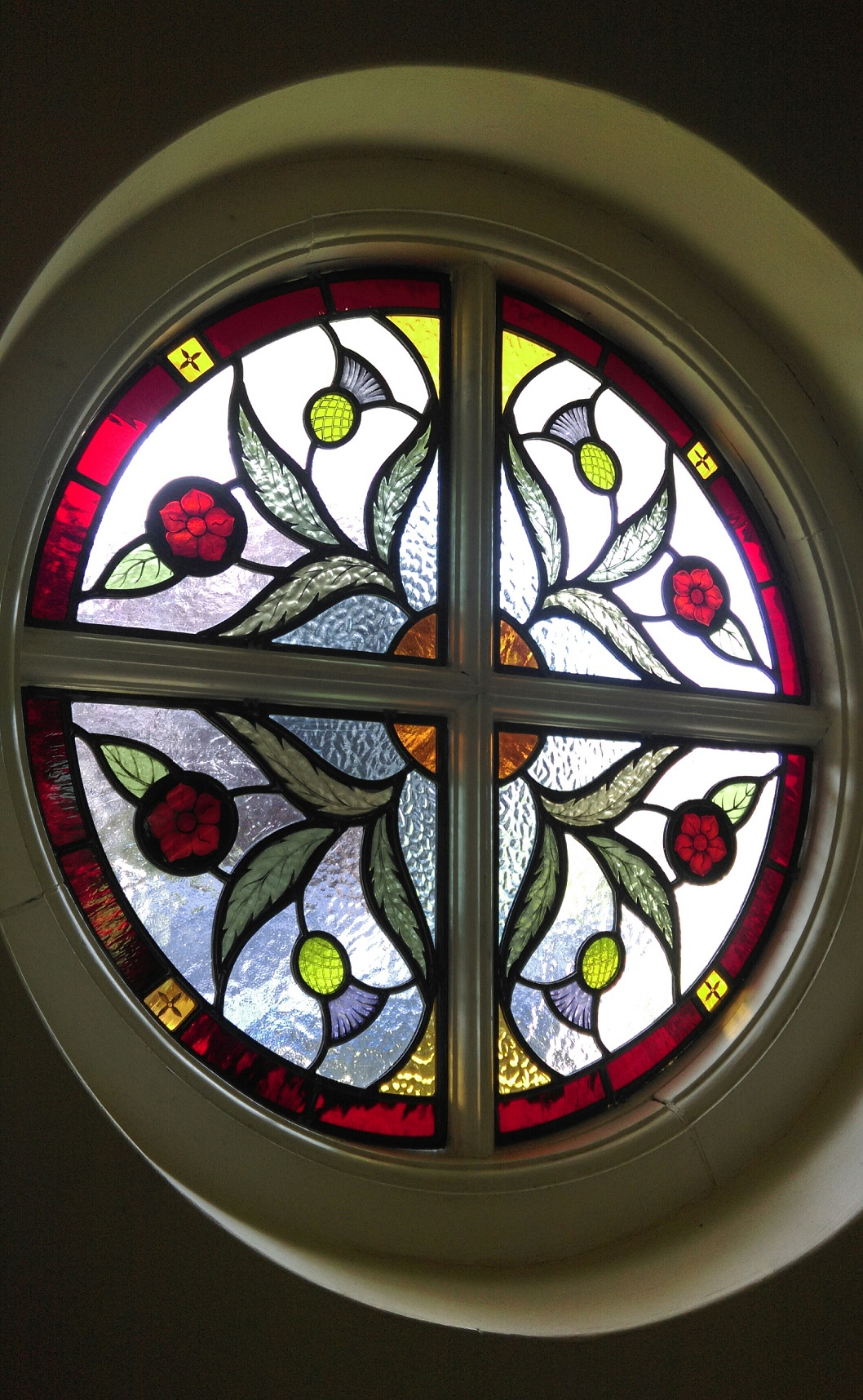 Round window featuring rose and thistle design for house in Chertsey, Surrey.