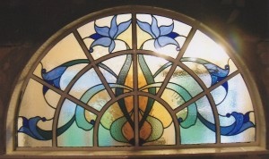A sweeping design within an arched window with blue Art Nouveau flowers.