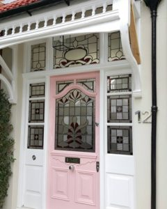 A pretty pink door complements striking red stained glass for house in North London.