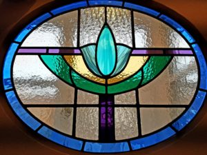 Art Deco oval door panel in shades of blue, purple and green.
