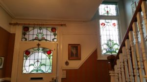 Original Edwardian panels in soft greens with red tulip style flowers for house in Ashford, Middlesex.