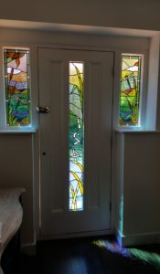Three water inspired stained glass panels featuring dragonflies for house in Ripley, Surrey.