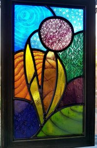 A contemporary stained glass design depicting a stylised Allium flower.