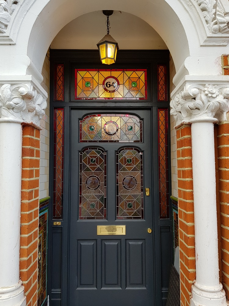 Traditional stained glass frontage with painted roundels for period property in south London.